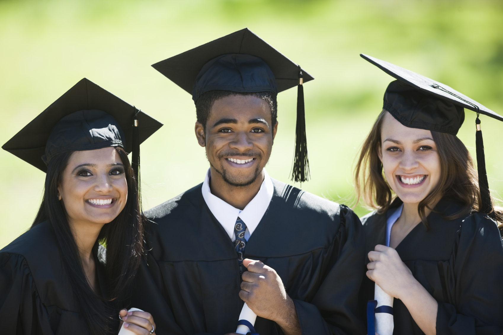 Three high school graduates wearing black gowns and mortar boards, smiling